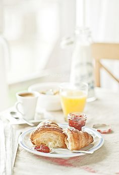 A warm, sunny, delightful weekend breakfast featuring croissants with jam, orange juice and coffee. #croissants #breakfast #brunch #food #pastry #jam #sunshine