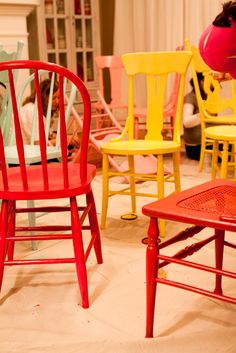 Different colored painted wooden chairs