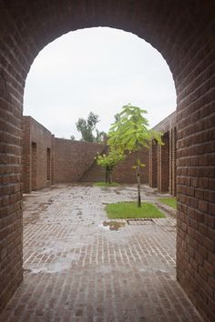 A labyrinth of brick walls, arches and courtyards are protected from flooding behind a man-made embankment at this open-air community centre in rural Bangladesh