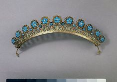 Three-colour gold tiara with swags of leaves and flowers surmounted by a row of large flowers formed by clusters of turquoises surrounded by cannetille work with a small diamond in the centre. It has been converted from a frontlet ornament of c.1805 and a French import mark and French design registry mark are on the loop at each end.
