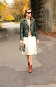 Layer a turtleneck sweater under a leather jacket for a chic fall look. Blogger Penny Pincher Fashion adds a feminine twist to the look by pairing a midi skirt and boots.