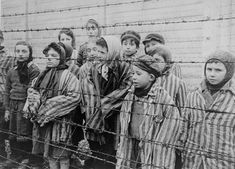 Jewish children, kept alive in the Auschwitz II (Birkenau) concentration camp, pose in concentration camp uniforms between two rows of barbed wire fencing after liberation. Still from a postwar Soviet film.