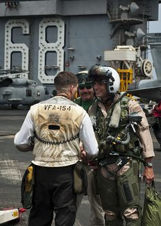 GULF OF OMAN (Aug. 28, 2013) – Capt. Rob Osterhoudt, deputy commander, Carrier Air Wing 11, right, shakes hands with Sailors on the flight deck of the aircraft carrier USS Nimitz (CVN 68) before his milestone flight. Osterhoudt completed his 1,000th carrier arrested landing aboard Nimitz Aug. 28. Nimitz Strike Group is deployed to the U.S. 5th Fleet area of responsibility conducting maritime security operations, theater security cooperation efforts and support missions for Operation Enduring Fr…