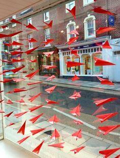 Window display with 100 red paper airplanes. #retail #merchandising #windowdisplay #paper