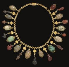 """A COLLECTION OF EGYPTIAN AMULETS   NEW KINGDOM TO ROMAN PERIOD, 16TH CENTURY B.C.-2ND CENTURY A.D.   Including thirteen scarabs of faience, steatite, and carnelian, some with motifs and inscriptions on their undersides; three heart amulets of haematite, carnelian and red jasper; a lapis lazuli vulture; an agate and a carnelian djed-pillar; a black stone facing head; a carnelian mano fica, a carnelian head, and a red jasper crouching deity; mounted together in a Egyptian revival gold necklace"""
