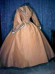 Majestic Civil War Era Two Piece Dress  blockquote>A marvelous classic circa 1865 lady's two piece golden russet colored silk faille dress.   The stayed bodice is lined with a tan polished cotton, has front darts, a hook and eye inner cinch waistband and eight original fancy metal buttons at the front closure. Piped at the neck, drop shoulders, waist and cuff hems. A center seam V back construction with a deep split tail.   The wonderful full pagoda sleeves are lined and faced in a white silk. A