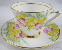 Phoenix Daffodil Cup and Saucer    French style cup and saucer with pink and yellow daffodil pattern on both sides of cup.