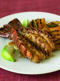 Grilled lobster tail with tropical fruit.Butterflied lobster tail with pineapple,mango and bananas grilled on gas grill.