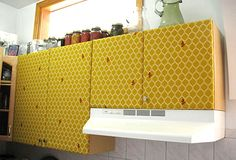 covering the surface of your cupboard doors with the fabric of your selection ~ I believe I would cover a smaller panel of cardboard with fabric and perhaps tack that on, leaving a framing of cabinet around the print.