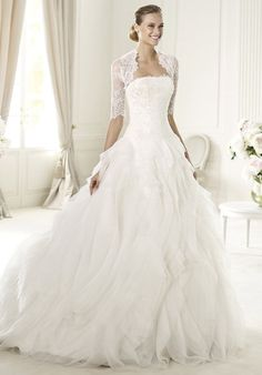 There is romance in each and every detail of Ulua wedding dress by Pronovias 2013. This tulle and organza off-the-shoulder design has a Chantilly lace bodice and a jacket with sleeves in the same fabric. This princess cut dress has a skirt with circular frills and is close fitting to the hip.