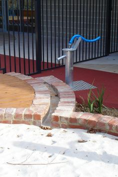 Water Features in the Preschool Play Space. Water pump with path to sand pit.