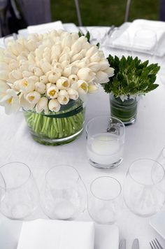 A white tablecloth gains visual interest with tightly  packed white tulips and stars of bethlehem.