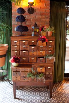 vintage library card catalogue used as escort card display.  some drawers are filled with fresh herb plantings while others have dahlia arrangements in coral, peach and burgundy. (photo courtesy of Kathi Littwin Photography - www.kathilittwin.com)