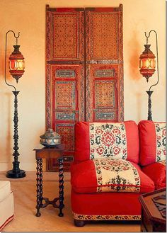 bohemian jewel tones: red orange trimmed furniture and gold ethnic lamps for living room