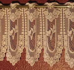 """""""Andrea"""" is a heavier weight Lace that is imported from Germany.  The Valance and Tiers can be used by themselves or together.  The Valance comes in a 11"""" height and the Tier is 23"""".  Fits up to 1/2"""" diameter rods.  No sewing necessary.  This pattern is available in  Beige (slightly darker than Ecru) and White.  100% washable poly.  It can be gathered up to 2 1/2 times if more fullness if desired."""