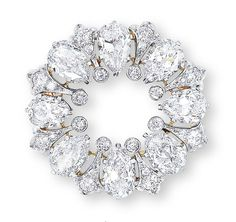 A DIAMOND BROOCH, BY TIFFANY & Co.   Of circular form, set with eight pear-shaped diamonds, spaced by diamond-set fleur-de-lis, accented by collet-set diamond details, mounted in platinum and 18k yellow gold, 3.4 cm in diameter  Signed Tiffany & Co.