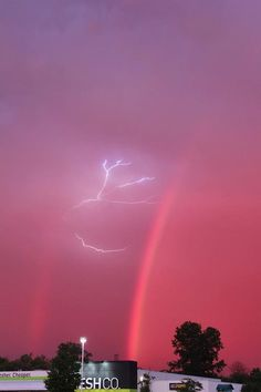 Lightning between a double rainbow during a thunderstorm.