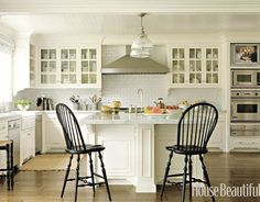 Subway tile backdrop, glass cabinets,white countertops