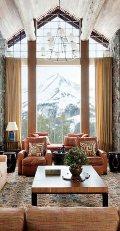 A snow capped mountain serves as a dramatic focal point for a Big Sky, Montana, living room decorated by Michael S. Smith. Locati Architects