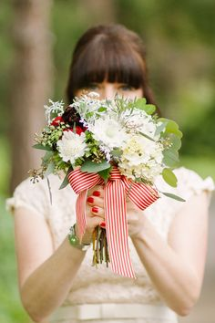 Yes to a red and white striped ribbon around the bride's bouquet + chic red nails!