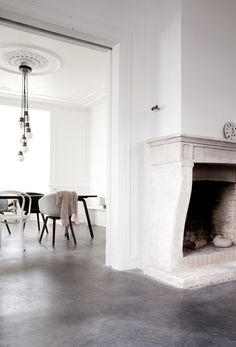 Fireplace, white walls, chandelier, dining table
