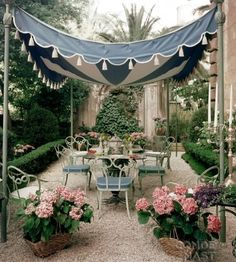 Navy tent with striped underside and white scallop trim and tassels. Combine it with swirly chairs, teeny hedges, and a lovely stone wall for backyard perfection.