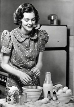 A cheerful 1930s gal whips up something yummy (perhaps a cake?) in this charming vintage photo. #1930s #vintage #kitchen #women #homemaker #1930s #thirties #cooking #homemaker #baking #baker #food