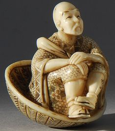 IVORY NETSUKE Depicting a man seated in a large straw hat.