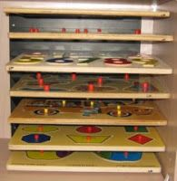 Kreative Resources: Storage idea for puzzles - - a metal paper sorting secured to shelf back.  Would work for  the toddler puzzles better than what JD built.