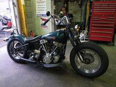 dark green panhead hardtail springer custom with small yellow headlight