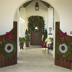 Jolly Welcoming: This home stays festive without being fussy or overwhelming. Soften a gated entryway with matching fir wreaths adorned with silver balls. Keep outdoor decorations fresh and simple with potted poinsettias and luscious greenery over the front door. Wreath and greenery available at floral or home supply stores. Ribbon and balls available at craft supply stores.
