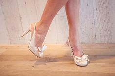 Bows on toes, a white pair of BHLDN heels. Photo by Breanna Saxon