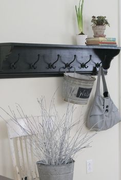 by the kitchen door? Love the shelf. Maybe use antique hooks