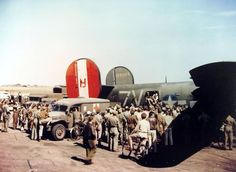 "Wounded aircrewmen are helped off B-24H Liberator ""Liberty Lib"" of the US 752nd Bomb Squadron at Horsham St Faith, Norfolk, England, after a raid on the Dornier factory at Lubeck, Germany, Aug 25 1944. Note the WC54 Ambulance. (US National Archives)"