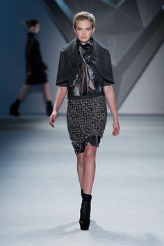 Charcoal melton cape over black vault print silk chiffon high neck sleeveless dress with crystal mesh skirt.