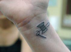 small  cute needle and thread tattoo