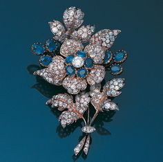 A late 19th century sapphire and diamond floral spray brooch  The single flowerhead mounted en tremblant with a central brilliant-cut diamond within a border of oval mixed-cut sapphires and pavé-set old brilliant-cut diamond petals, the leaves and stem similarly set and highlighted by six oval mixed-cut sapphire buds