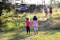 Two young girls holding hands, ready to go on a safari in Kenya's maasai mara.  family safari holidays/www.asiliaafrica.com