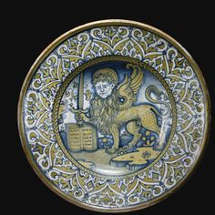 An Italian majolica dish, c.1535-50; at the centre is the symbol of St Mark the Evangelist: a winged lion, with, unusually, a halo-crowned human face; the book represent St Mark's gospel, and the lion holds a sword, symbol of the Christian willingness to defend Christianity.
