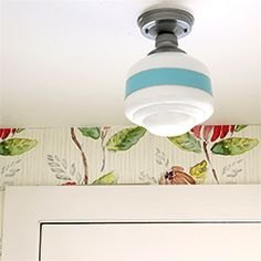 Transform a plain light fixture into a high end looking decorative schoolhouse light with some paint.