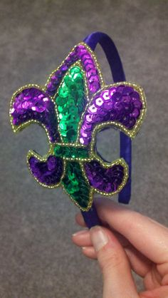 "It's Carnival Time!  Perfect headband to wear to balls and parades.  Purple, Green, and Gold fleur de lis 4.5"" x 3"".  On a purple or black headband.  $15 each"