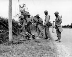 July, 13, 1944. Normandy. American soldiers with two mine detectors at the foot of an electric pole.