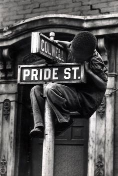 """W. Eugene Smith  """"Pittsburgh (Boy Hanging on Colwell & Pride St. Sign) 1955-56"""""""