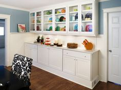 This dining room's L-shape layout once felt awkward and useless. To make it functional, built-in cabinets were added on the long wall. They provide extra storage and plenty of display space for some colorful, festive dinnerware.