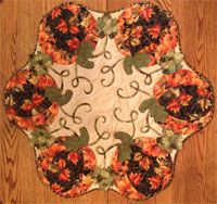 """Pumpkin Leaves All Around Table Mat/Wallhanging Pattern by The Quilted Garden at KayeWood.com. Dimensional leaves and swirly vines complete this topper. Applique at the quilting stage makes for a quickie project. App 34"""" in diameter. http://www.kayewood.com/item/Pumpkin_Leaves_All_Around_Table_Mat_Wallhanging_Pattern/3486 $11.00"""