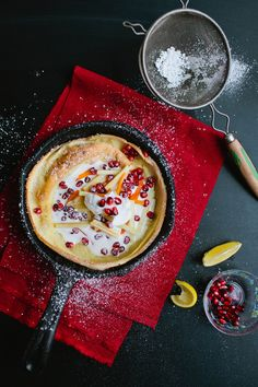 A festive breakfast idea: a Dutch baby pancake topped with pomegranate seeds.