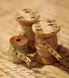Spools...love this! I have been using old spools for my ribbon remnants. Love the idea of old book pages or sheet music to cover the tops and bottoms....