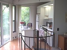 A small kitchen but windows from floor to ceiling with a view towards the lake. Remember, this is a two story circular unit. The circular stairways lead to a downstairs bedroom and bath.
