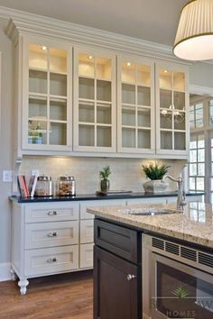 white cabinets with glass and black island