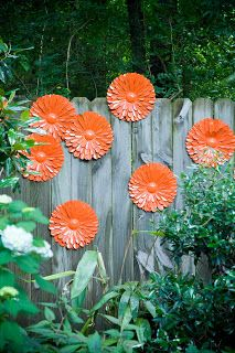 DIY fence art.  Spray paint dollar store metal flowers to brighten up a dreary fence.  Amazing what a little pop of color can do!